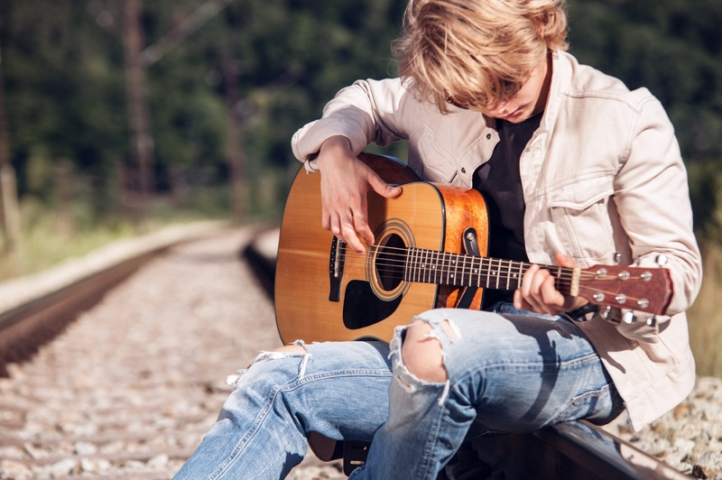 Man Playing Guitar Train Tracks Ripped Jeans White Jacket
