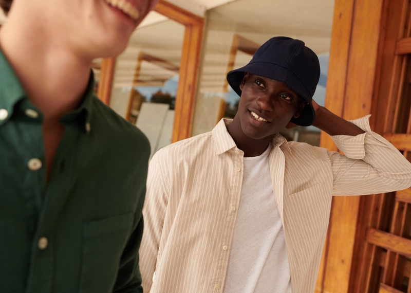 All smiles, Charles Oduro wears a bucket hat and striped shirt from Octobre's Motel Paradise collection.