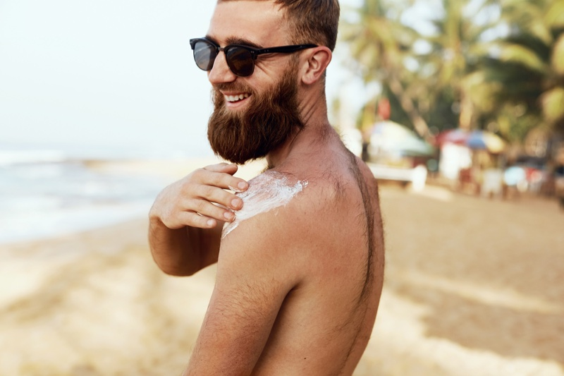Smiling Man Applying Sunscreen Beach