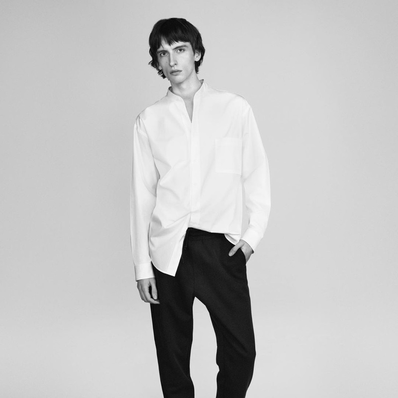 Benno Bulang dons a crisp white band-collar shirt with black trousers for UNIQLO +J's spring 2021 campaign.