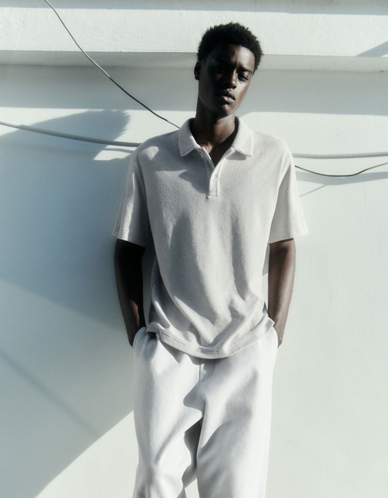 Front and center, Babacar N'doye wears a COS terry polo shirt with elasticated tapered leg trousers.