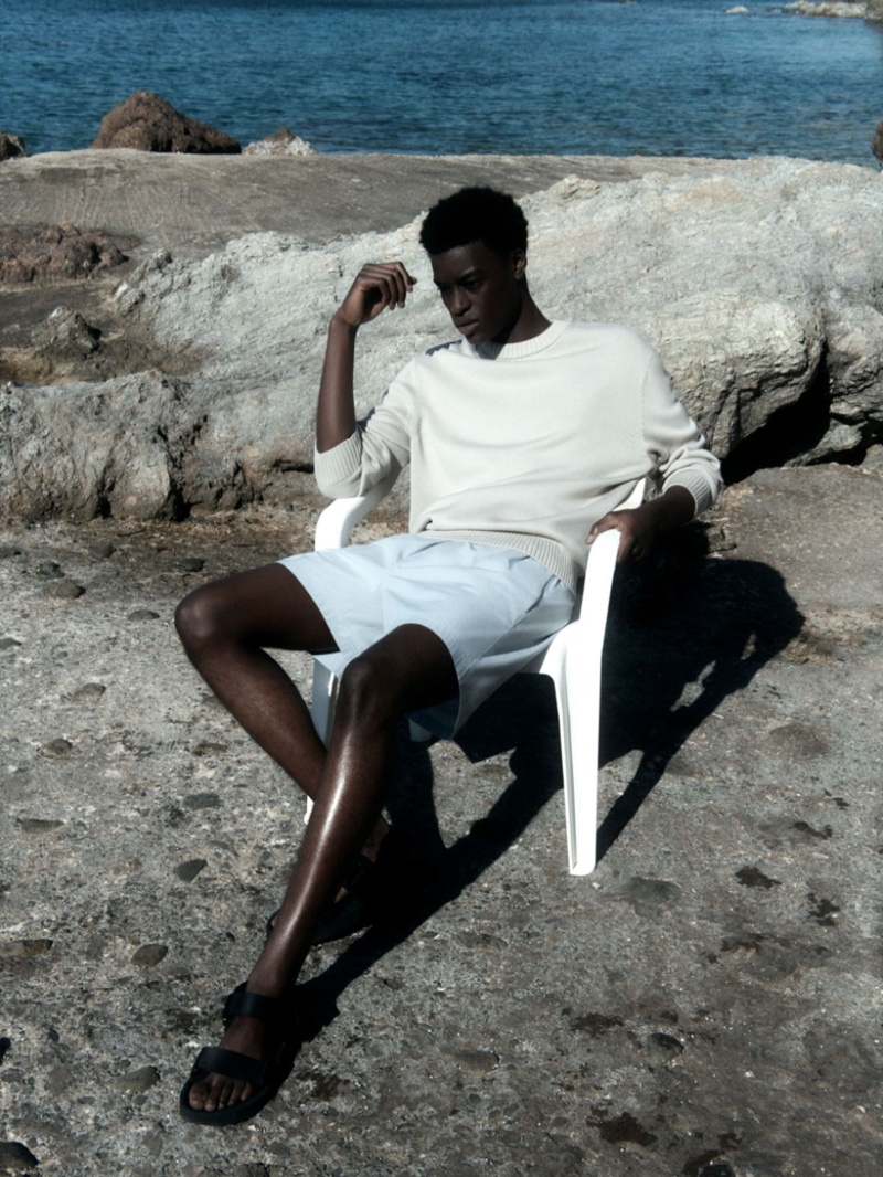Relaxing, Babacar N'doye sports a COS relaxed-fit jumper with drawstring shorts and leather sandals.