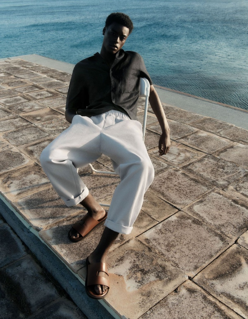 Babacar N'doye rocks a COS camp collar short-sleeve shirt with elasticated tapered leg trousers.