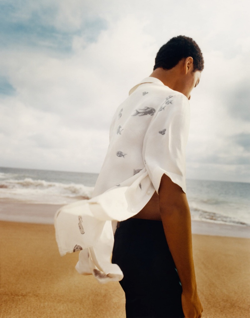 Hitting the beach, Jecardi Sykes sports a printed shirt from Dior Men's 2021 beachwear capsule collection.