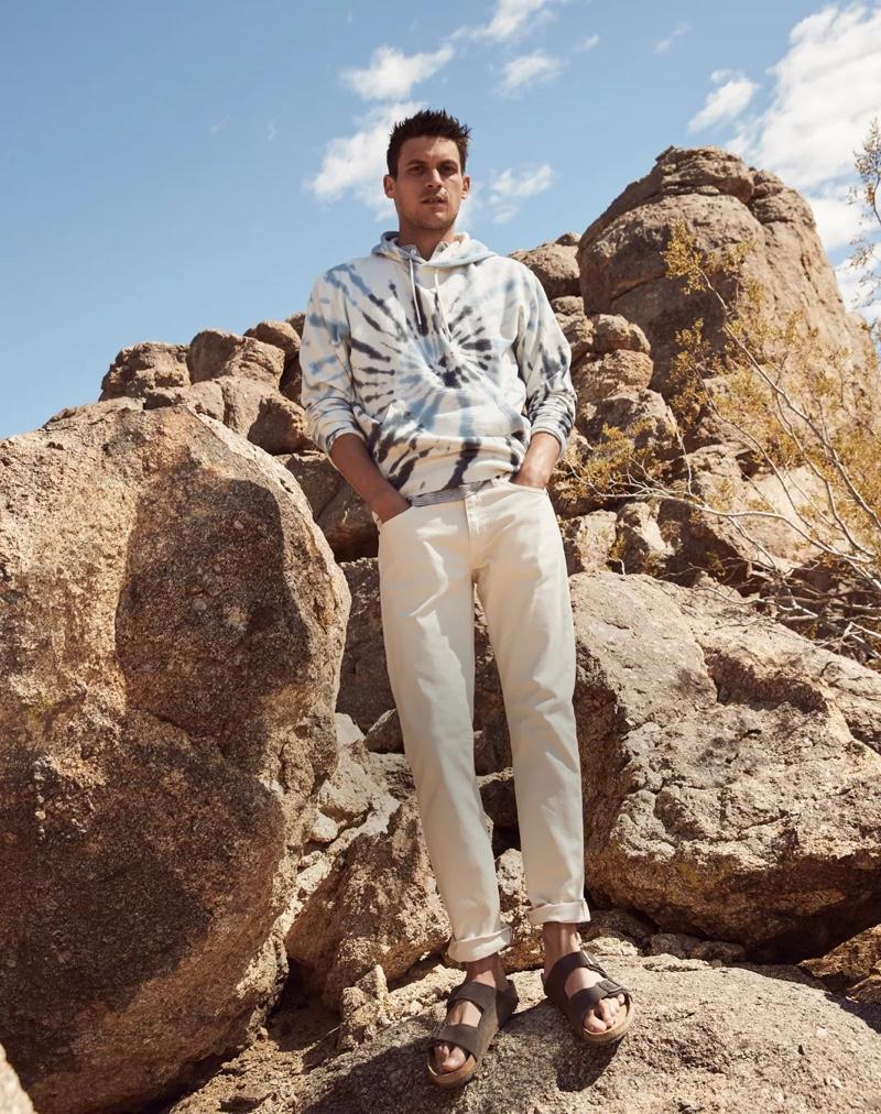 Embracing the tie-dye trend, Miles Garber sports a J.Crew tie-dye hoodie with 484 slim-fit, five-pocket pants, and Birkenstock sandals.