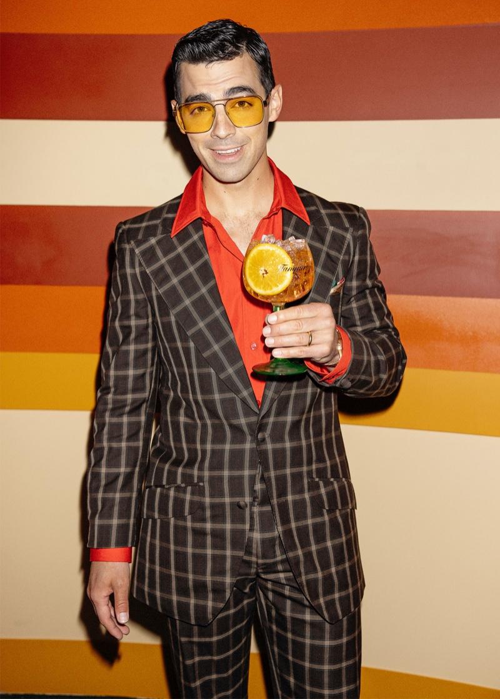 Holding a glass of Tanqueray Sevilla Orange, Joe Jonas goes retro as a news anchor.