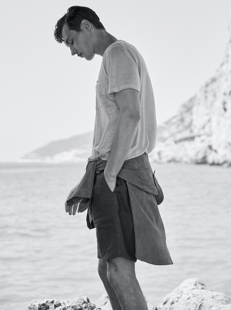 Appearing in a black and white image, Kit Butler dons a suede overshirt, 100% linen t-shirt, and technical cotton poplin Bermuda shorts from Massimo Dutti.