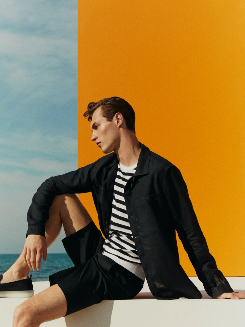 Delivering a side profile, Kit Butler sports a Massimo Dutti 100% linen overshirt, nautical stripe cotton knit t-shirt, technical cotton poplin Bermuda shorts, and sporty blue leather loafers.