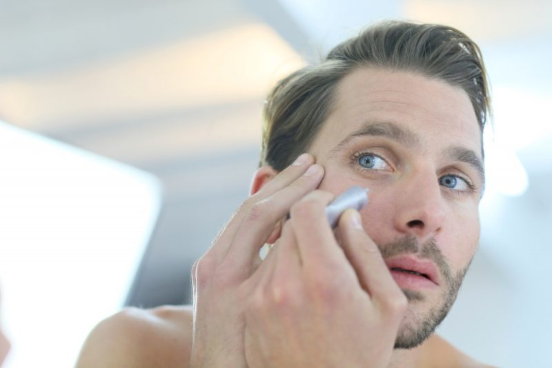 Man in front of mirror using cosmetic cream
