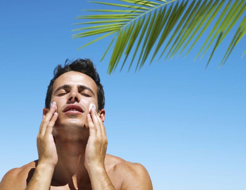 Man Putting Sun Skin Protection In Summer on beach