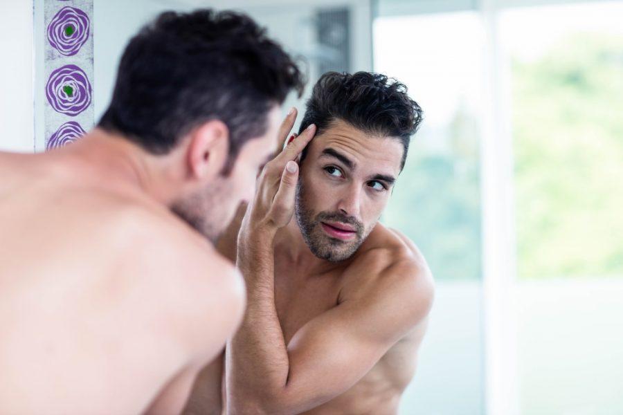 Handsome man looking at his hair in bathroom