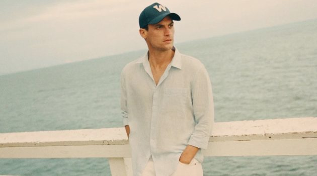 Donning sleek summer style, Miles Garber wears a linen shirt and white pants from Zara.