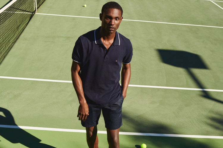 Sporting a navy polo, Victor Ndigwe models a tennis look from Tommy Hilfiger.