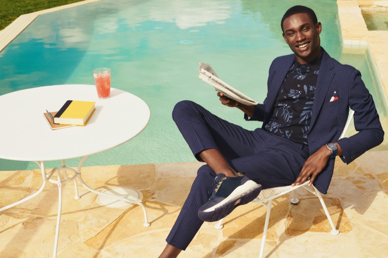 Relaxing poolside, Victor Ndigwe embraces tailoring in a sharp Tommy Hilfiger suit.