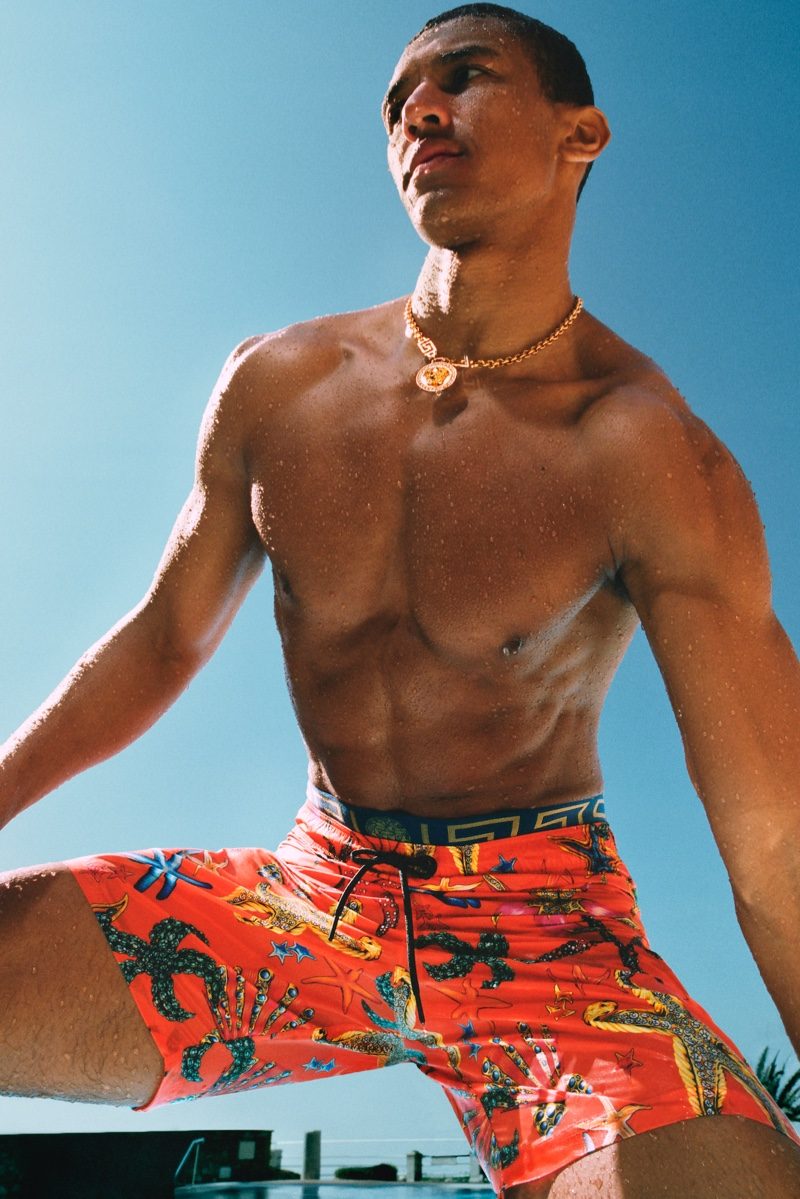 Loïc Namigandet makes a splash in a gold necklace and printed swim shorts for Versace's La Vacanza campaign.