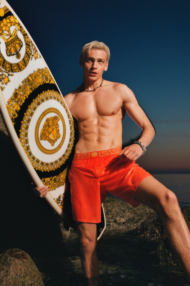Taking hold of a Versace surfboard and wearing red swim shorts, Lucas Barski fronts the Versace La Vacanza campaign.