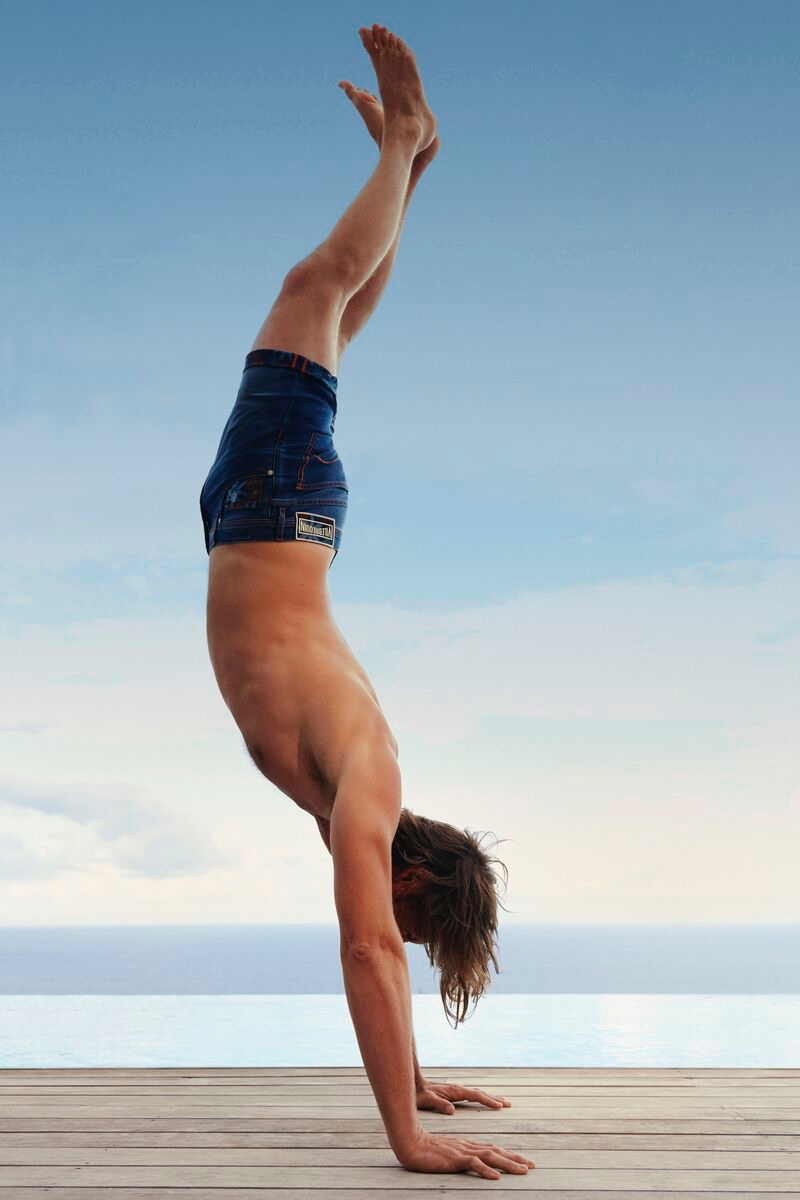 Doing a handstand, James Crabtree rocks Vilebrequin's flat belt swim trunks.