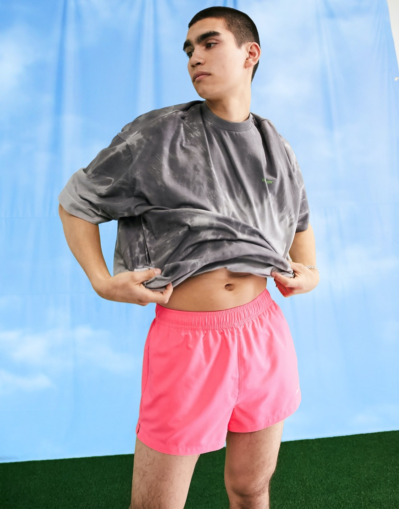 Standing out, model Del Winder sports ASOS's COLLUSION short swim shorts in neon pink.