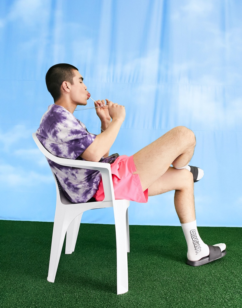Showcasing the latest trends, Del Winder wears a tie-dye t-shirt with ASOS's COLLUSION short swim shorts in neon pink.