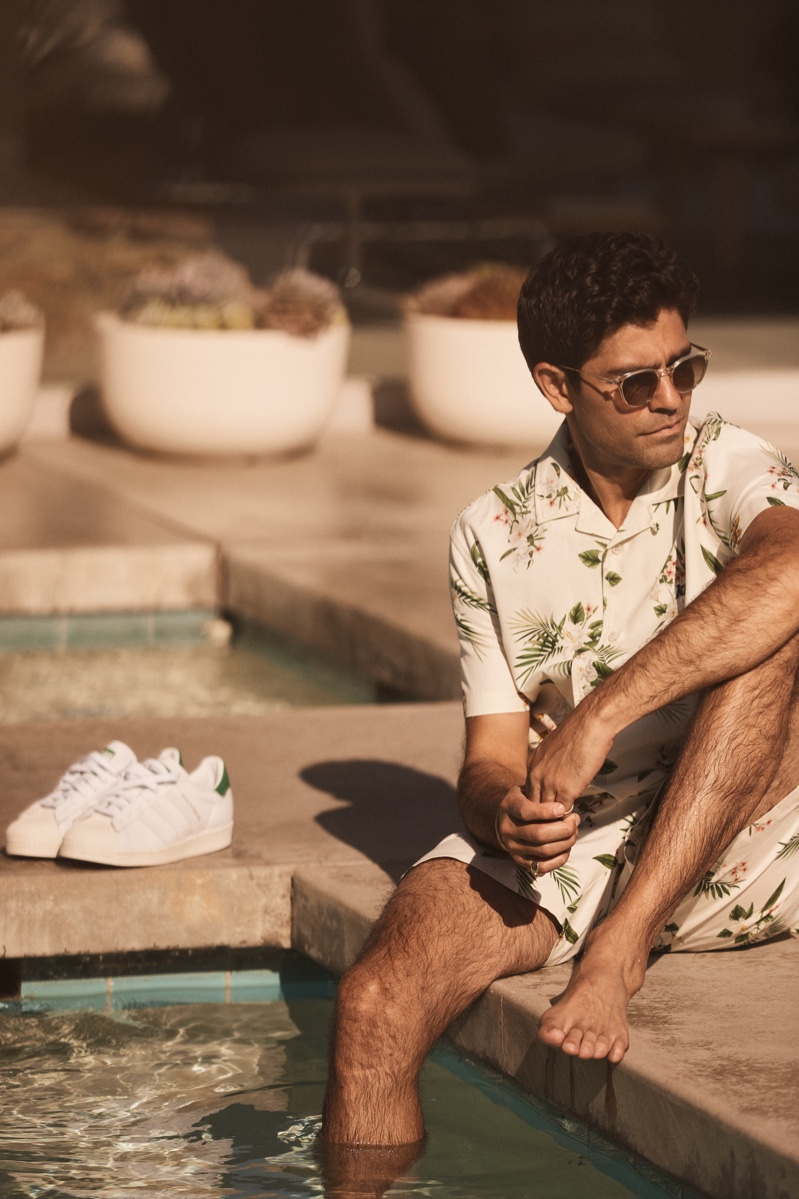 Relaxing poolside, Adrian Grenier wears a matching shirt and shorts with a tropical print for Kith's summer 2021 campaign.