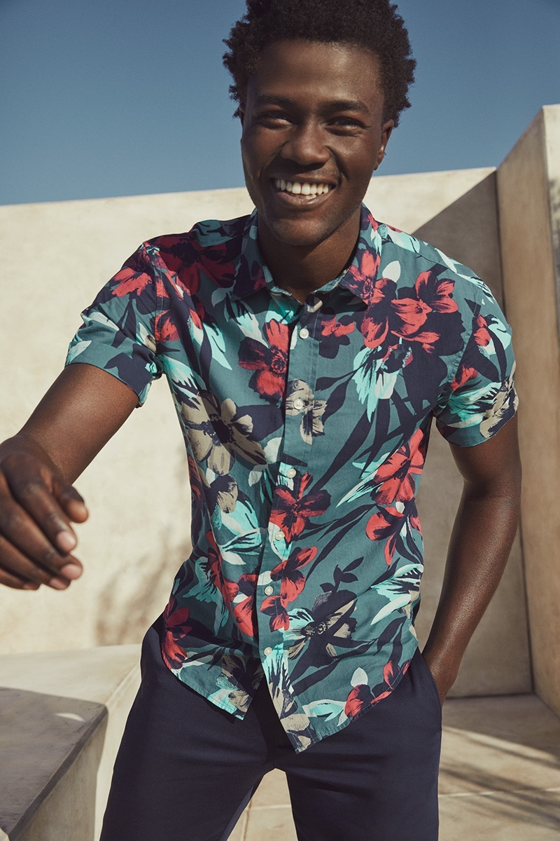Cheesing ear to ear, Remi Chester spreads joy in a tropical print short-sleeve shirt from Banana Republic.