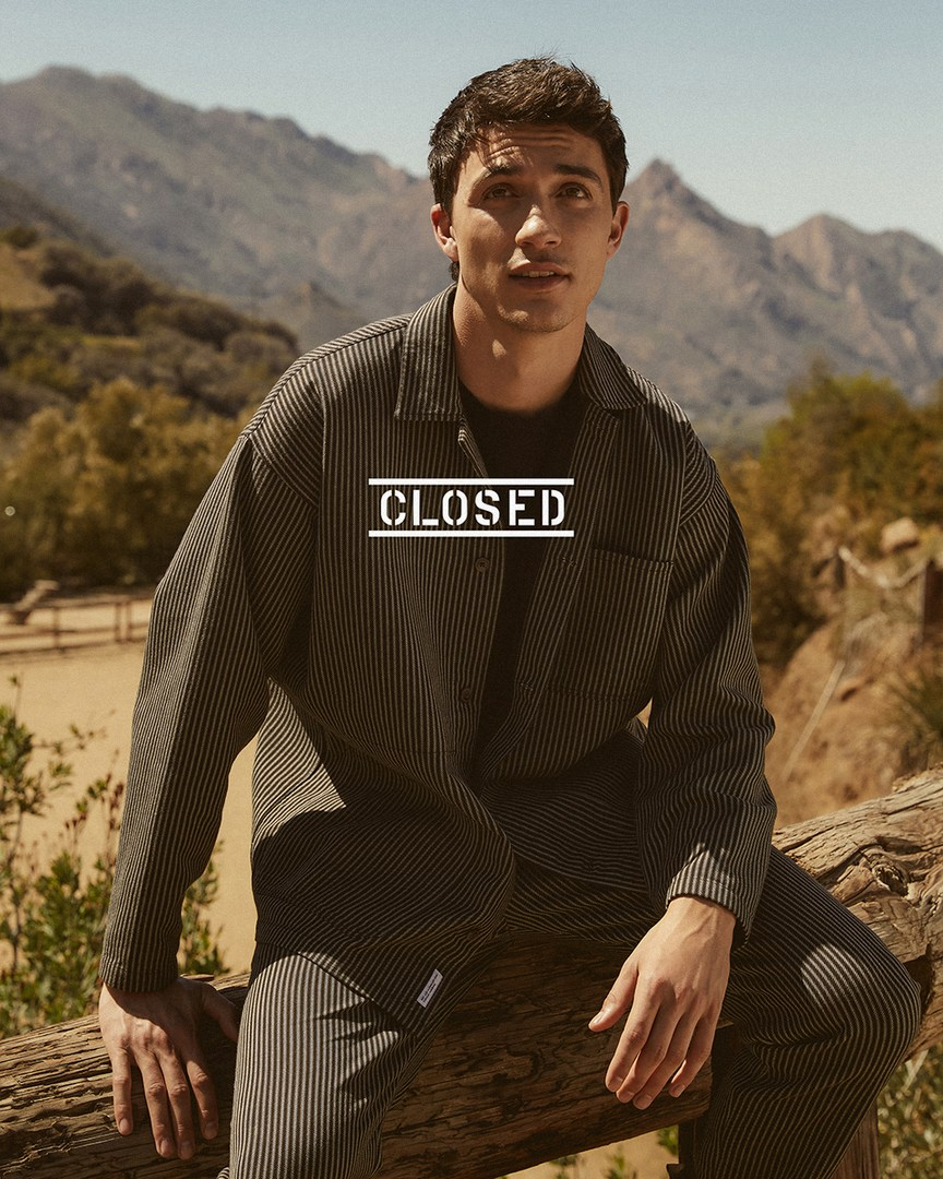 Jacob Bixenman wears a matching striped overshirt and pants for Closed's summer 2021 campaign.