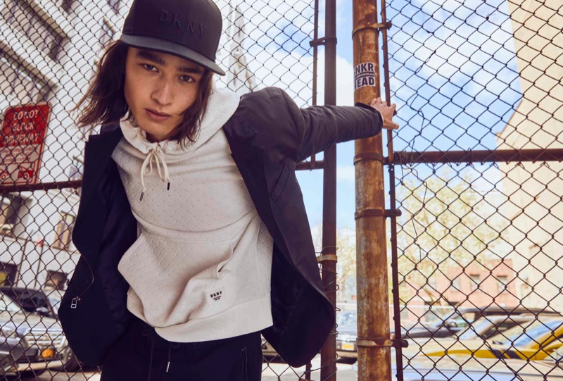 Layering for the season, Peter Meyer sports a hoodie with a jacket and cap from DKNY's fall-winter 2021 men's collection.