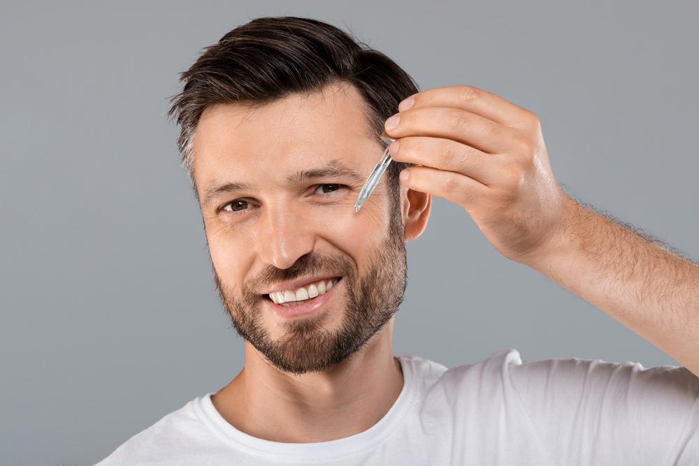 Face Serum Man Using Dropper