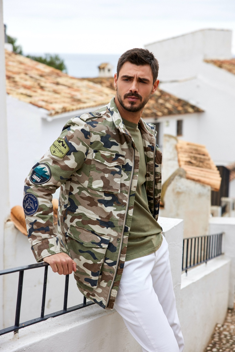 Rocking a camouflage jacket with white jeans, Francesco Monte fronts GUESS' summer 2021 men's campaign.