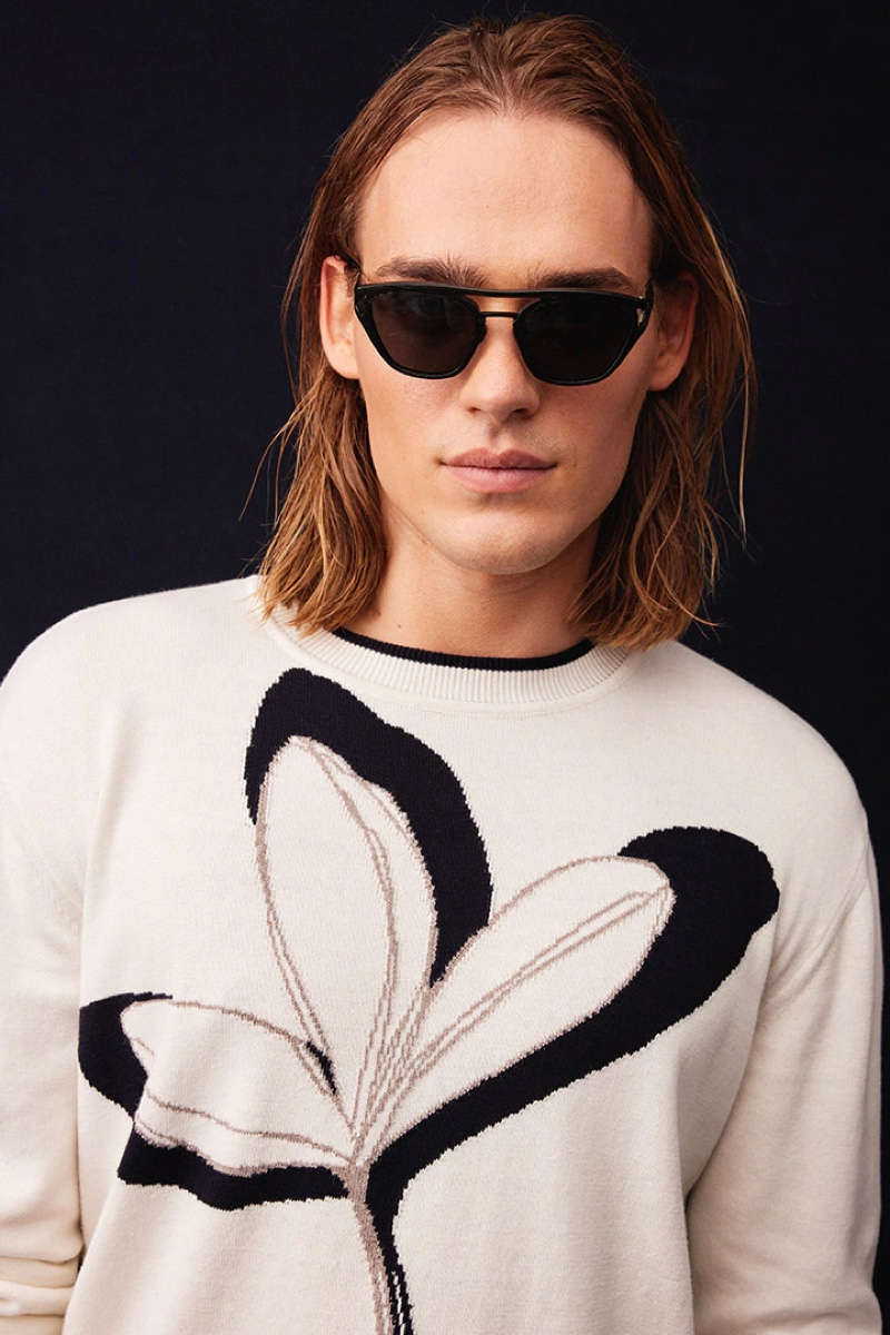 Ready for his close-up, Ton Heukels models a knit sweater and modern shades from Giorgio Armani's spring-summer 2022 collection.