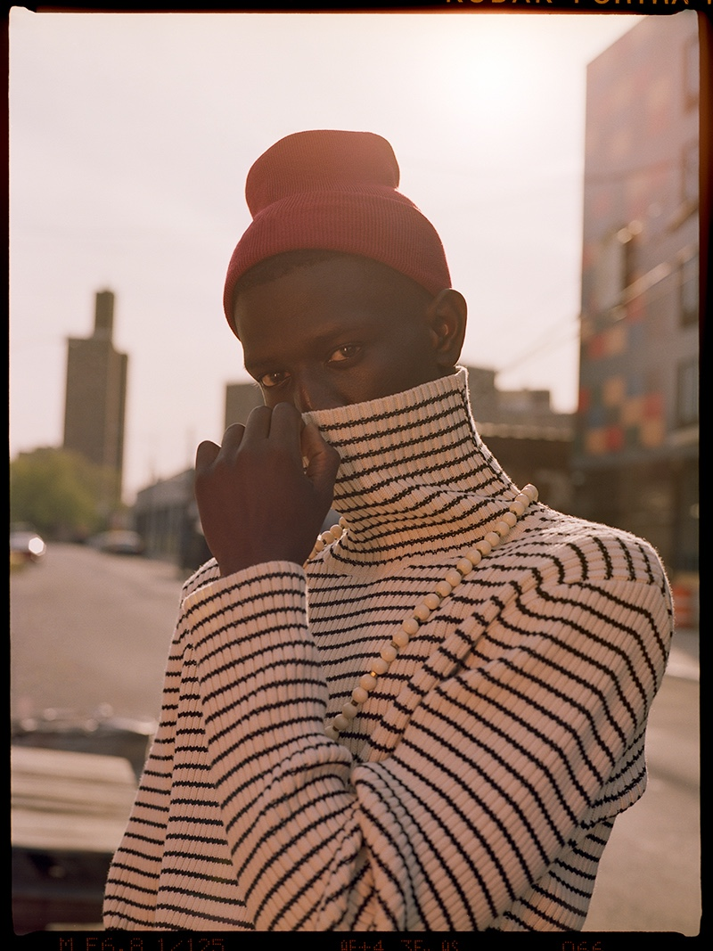Ibby wears striped turtleneck sweater Teddy Vonranson, beanie Lacoste, and necklace Vanessa's Vintage.