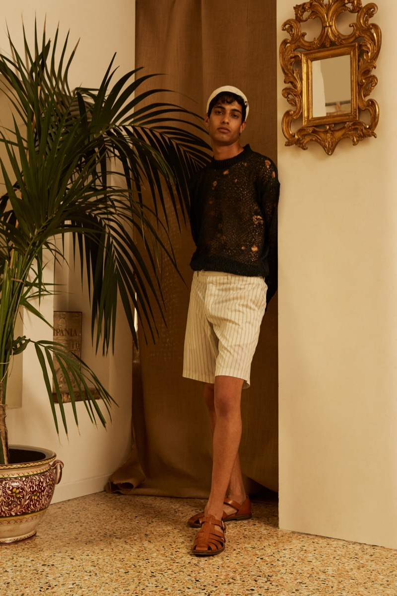 Modeling a spring-summer 2022 look from Luca Larenza, Matteo Tagliabue is pictured in a deconstructed sweater and striped shorts.