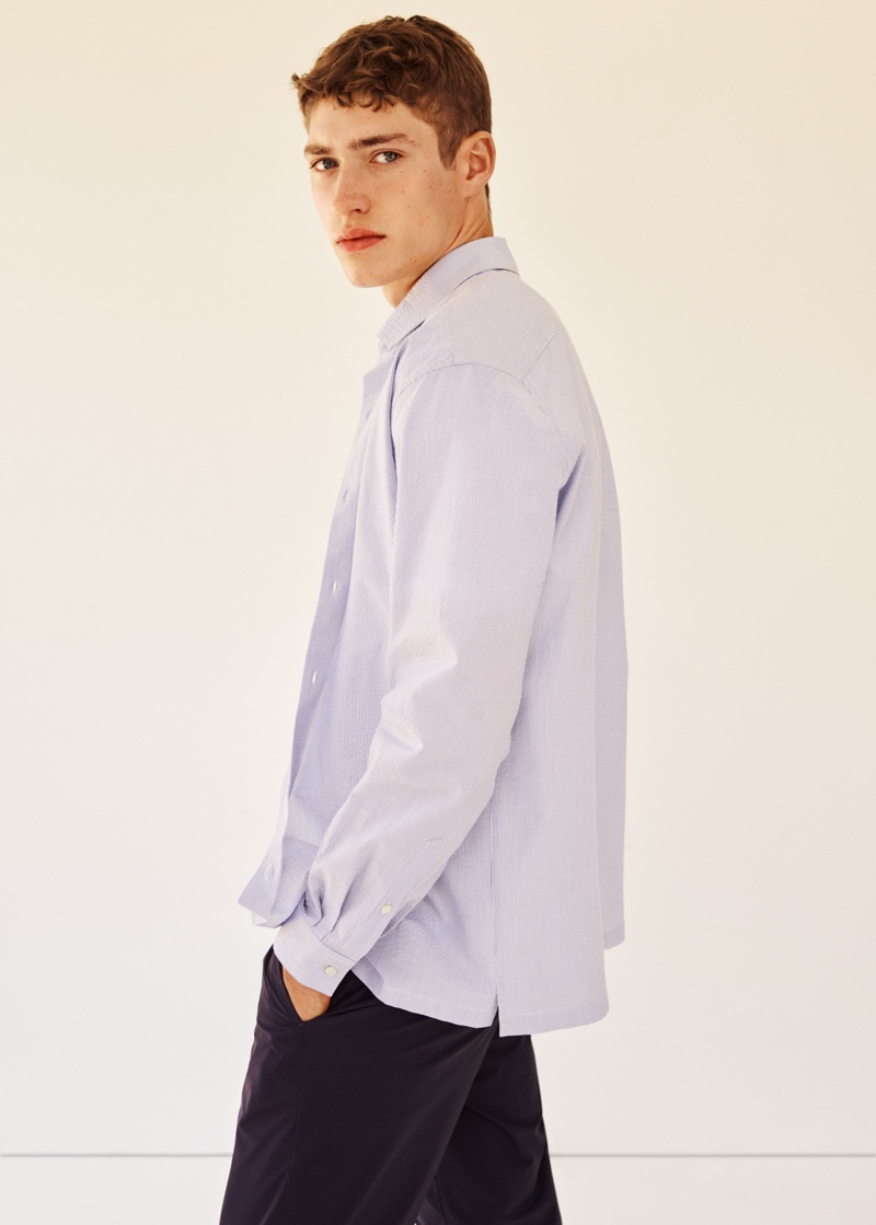 Photographed from the side, Valentin Humbroich wears an oversized shirt with trousers from Mango Man's Clean collection.