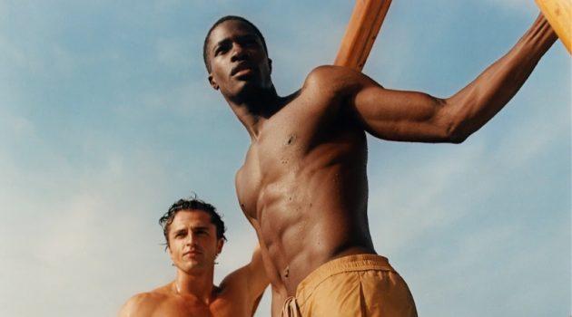 Models Alberto Perazzolo and Mukasa Kakonge sport swim shorts from Mango Man's summer 2021 collection.