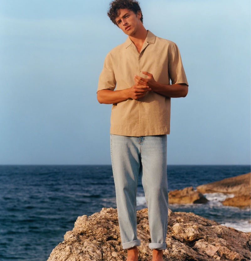 Alberto Perazzolo wears a Cuban-collared shirt with light wash jeans from Mango Man's summer 2021 collection.