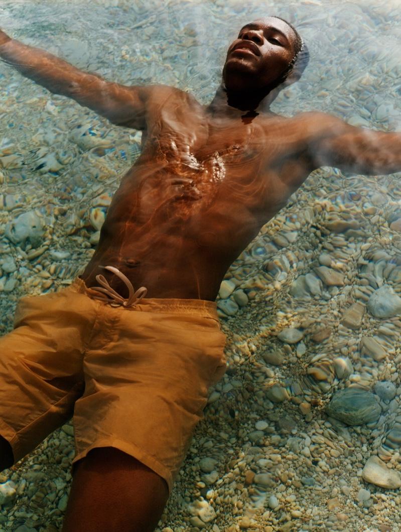 Taking a dip, Mukasa Kakonge models swim shorts from Mango Man's summer 2021 collection.