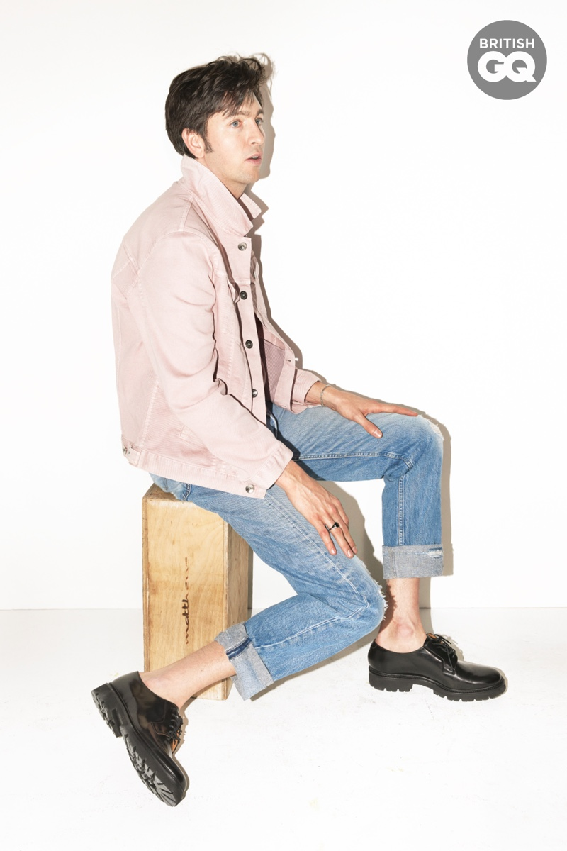 Hitting the photo studio, Nicholas Braun wears a Brunello Cucinelli jacket with Levi's jeans and Grenson shoes. The American actor also dons a ring by Miansai.