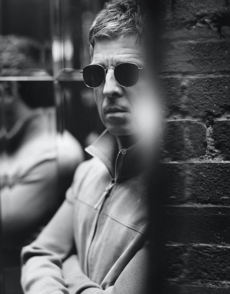 Appearing in a black and white image for Mr Porter, Noel Gallagher wears a Tom Ford suede and merino wool blouson jacket with Saint Laurent D-Frame silver-tone sunglasses.