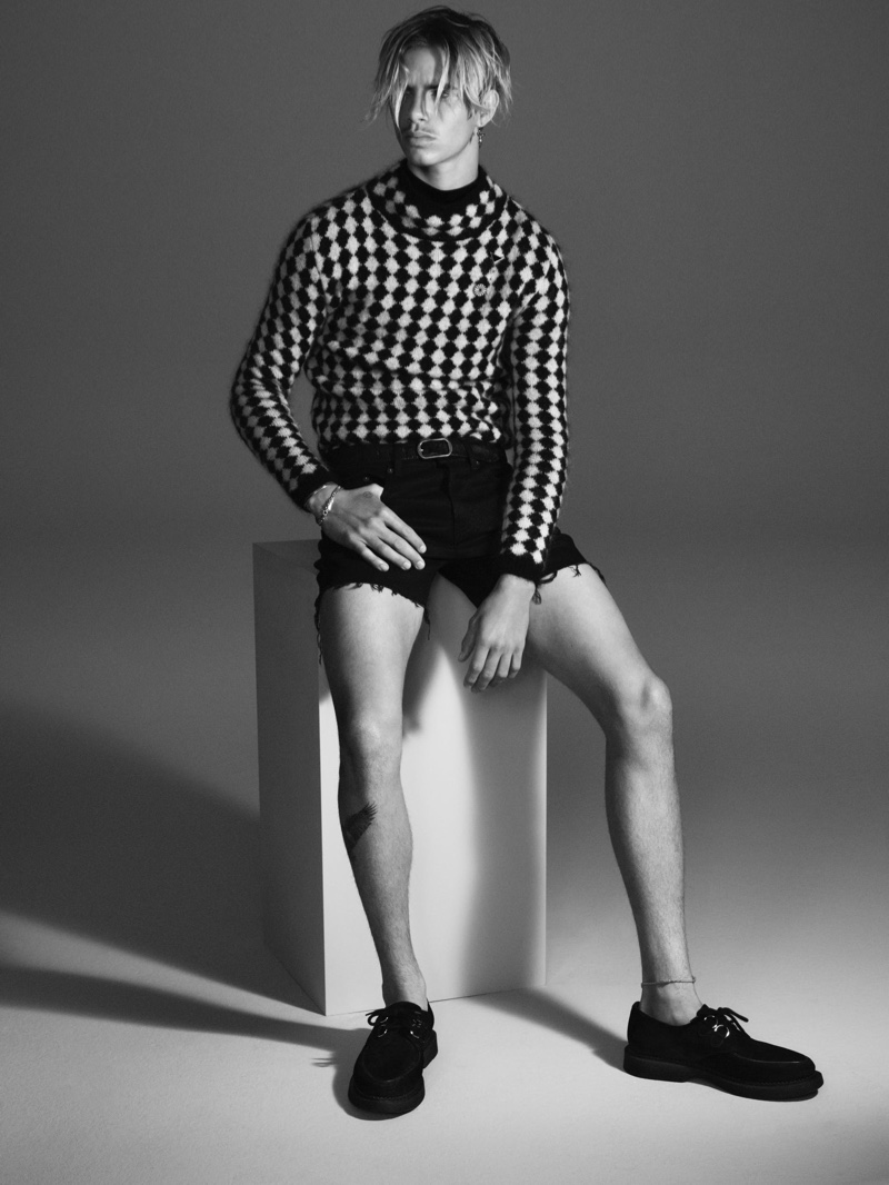 Donning a checkered knit and frayed cut-off denim shorts, Romeo Beckham stars in Saint Laurent's fall-winter 2021 men's campaign.