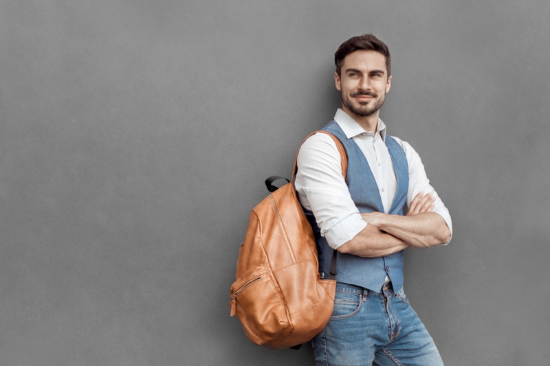 Smiling Man Vest Brown Backpack Jeans