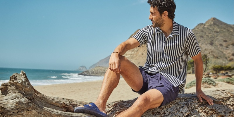 """Noah Mills relaxes in a Todd Snyder vertical stripe terry button-down polo and 7"""" weekend shorts with Freedom Moses sandals."""