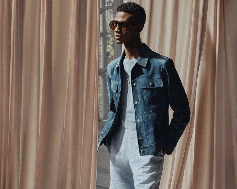 Model Jason Harderwijk dons a Tom Ford t-shirt with a blue suede trucker jacket, brown aviator-style tortoiseshell acetate sunglasses, and silk and linen-blend suit trousers