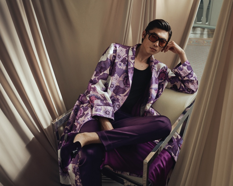 Relaxing, Hidetatsu Takeuchi wears a Tom Ford piped floral-print silk-twill robe with purple leather-trimmed velvet loafers and brown round-frame tortoiseshell acetate sunglasses.