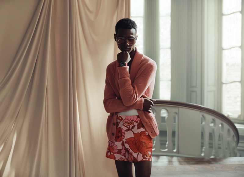Front and center, Jason Harderwijk wears Tom Ford's pink ribbed cashmere cardigan, gray round-frame acetate sunglasses, and slim-fit floral print swim shorts.