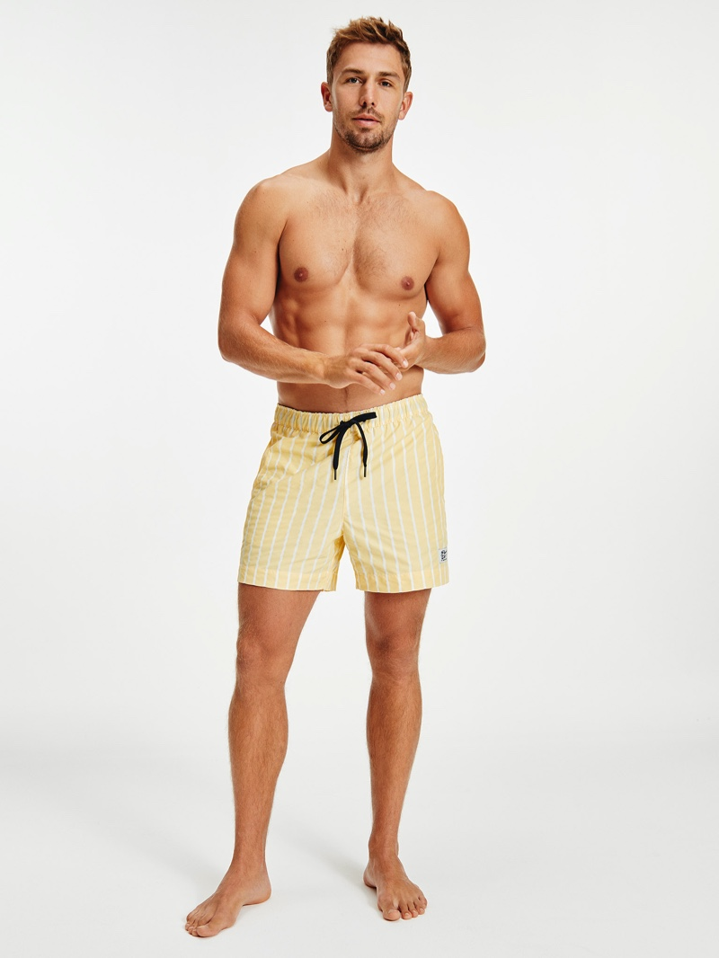 Front and center, James Yates models yellow striped swim trunks by Tommy Hilfiger.