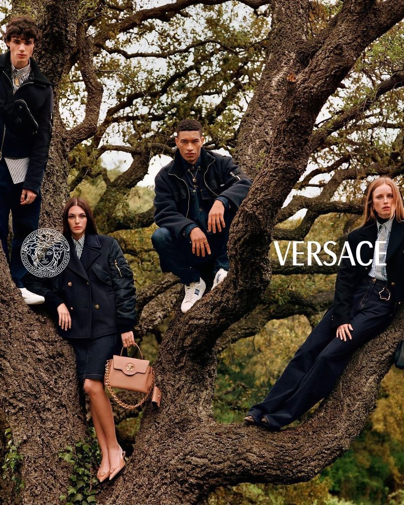 Posing in a large tree, models Fernando Lindez, Vittoria Ceretti, Raphael Balzer, and Rianne Van Rompaey come together for Versace's pre-fall 2021 campaign.