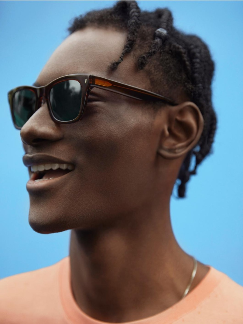 Photographed from the side, Youssouf Bamba takes delight in wearing Warby Parker's Harris sunglasses in Cacao Crystal.