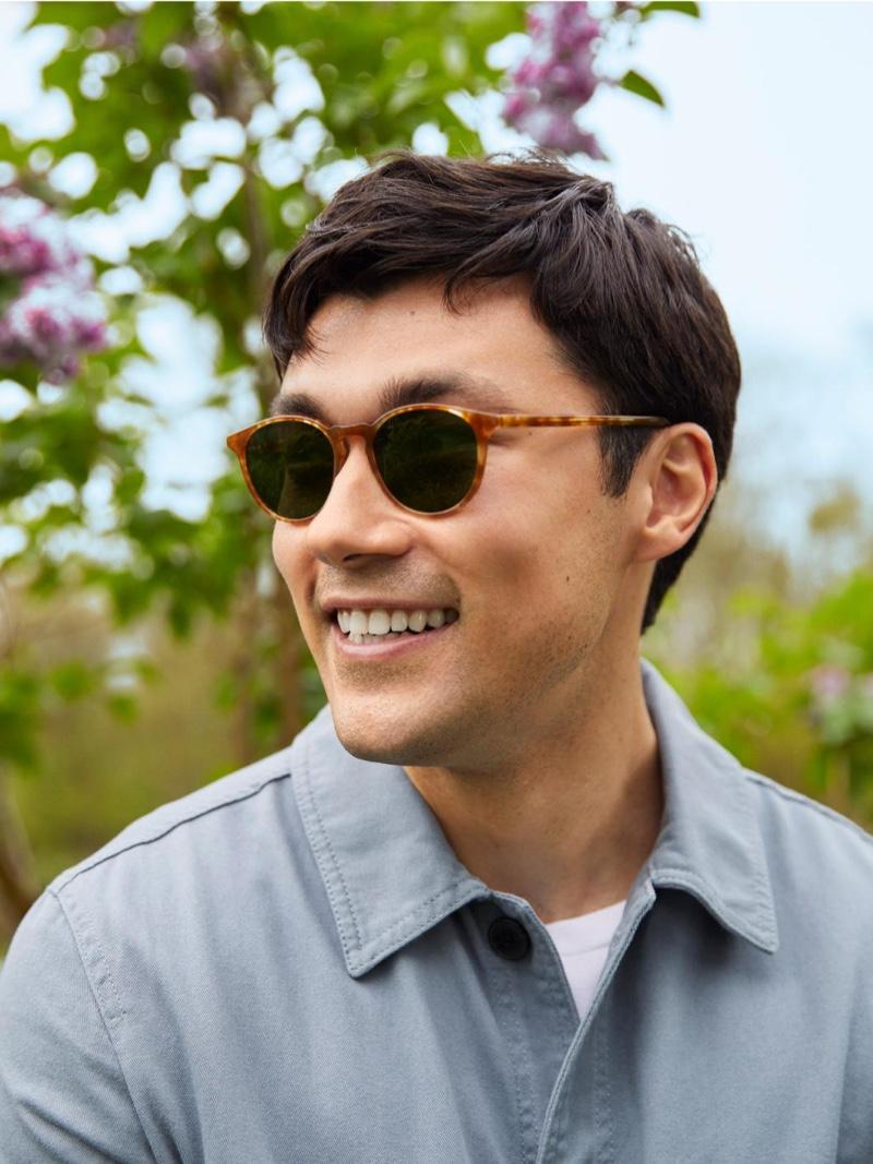 All smiles, Ruslan Aliiev models Warby Parker's Butler sunglasses in Butterscotch Tortoise.