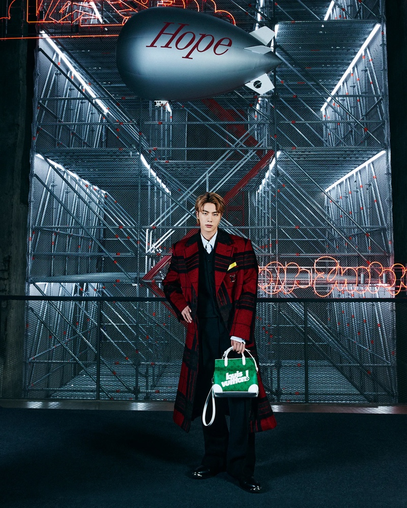 Jin dons a red and black check coat by Louis Vuitton.