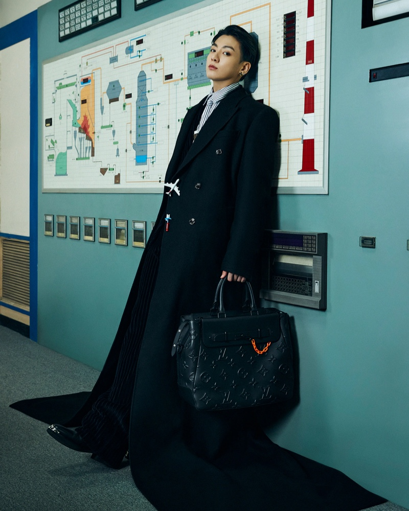 Jungkook makes a sartorial impression in a long tailored coat by Louis Vuitton.